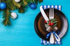 圣诞节桌与餐巾的餐位餐具、黑色的盘子、白色叉子和刀子、槲寄生装饰的小树枝和圣诞节 免版税图库摄影