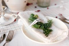 圣诞节桌:刀子和叉子、餐巾和圣诞树在一张木桌上分支 新年欢乐桌的` s装饰 库存照片