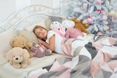 圣诞节梦想 儿童休眠 在圣诞树的小孩睡眠 在与玩具的床上的女孩 逗人喜爱的女孩 图库摄影