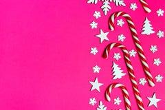 圣诞节棒棒糖在桃红色背景的行均匀地在与装饰雪花和星 平的位置和顶视图 库存照片