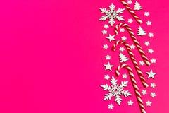 圣诞节棒棒糖在桃红色背景的行均匀地在与装饰雪花和星 平的位置和顶视图 图库摄影