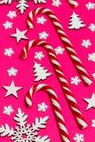 圣诞节棒棒糖在桃红色背景的行均匀地在与装饰雪花和星 平的位置和顶视图 免版税库存照片