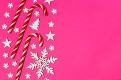 圣诞节棒棒糖在桃红色背景的行均匀地在与装饰雪花和星 平的位置和顶视图 免版税库存图片