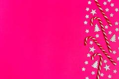 圣诞节棒棒糖在桃红色背景的行均匀地在与装饰雪花和星 平的位置和顶视图 库存图片