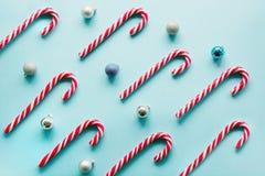 圣诞节棒棒糖在蓝色的行均匀地在 平的位置和顶视图 免版税库存图片