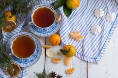 圣诞节森林上了凸边早晨多雪的线索宽冬天 中国黏土托起木饮用的糖表茶的茶壶二 一幅美丽的静物画用蜜桔和两个杯子热的茶 免版税库存图片