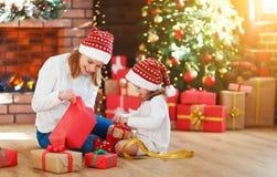 圣诞节森林上了凸边早晨多雪的线索宽冬天 家庭母亲和女儿打开,开放礼物 免版税库存照片