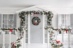圣诞节森林上了凸边早晨多雪的线索宽冬天 门廊有一个装饰的门的一个小屋与圣诞节花圈 木报道的神仙的森林房子雪传说的冬天 库存图片