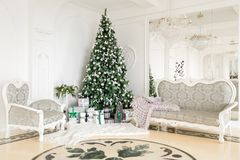 圣诞节森林上了凸边早晨多雪的线索宽冬天 与一个白色壁炉,装饰的树,明亮的沙发,大窗口的经典公寓 免版税图库摄影