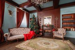 圣诞节森林上了凸边早晨多雪的线索宽冬天 与一盏白色壁炉、装饰的树、沙发、大窗口和枝形吊灯的经典公寓 库存图片
