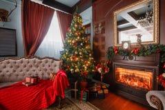 圣诞节森林上了凸边早晨多雪的线索宽冬天 与一盏白色壁炉、装饰的树、沙发、大窗口和枝形吊灯的经典公寓 免版税库存图片
