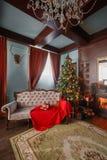 圣诞节森林上了凸边早晨多雪的线索宽冬天 与一盏白色壁炉、装饰的树、沙发、大窗口和枝形吊灯的经典公寓 库存照片