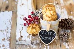 圣诞节椰子蛋白杏仁饼干用霍莉莓果和在白色木头的杉木锥体 库存照片
