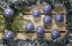 圣诞节概念新年度 与锥体的杉树分支在一个框架闪亮金属片、诗歌选和蓝色新年球在木板,上面 免版税图库摄影