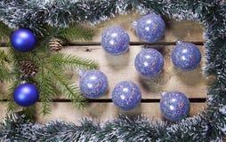 圣诞节概念新年度 与锥体的杉树分支在一个框架闪亮金属片、诗歌选和蓝色新年球在木板,上面 图库摄影