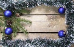 圣诞节概念新年度 与锥体的杉树分支在一个框架闪亮金属片、诗歌选和蓝色新年球在木板,上面 免版税库存图片