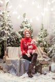 圣诞节概念母亲和儿子坐在红色套头衫和帽子的木摇摆在积雪的树前面 免版税图库摄影