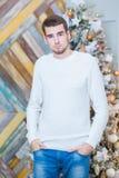 圣诞节概念,男性时尚 摆在豪华公寓的典雅的套头衫的英俊的年轻人装饰为 库存照片