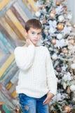 圣诞节概念,男性时尚 摆在豪华公寓的典雅的套头衫的英俊的年轻男孩装饰为 库存照片