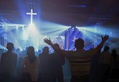 圣诞节概念:被弄脏的基督徒会众崇拜上帝一起在音乐阶段前面的教会光线影响的大厅和里 库存图片