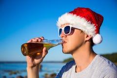 圣诞节概念-人画象圣诞老人帽子饮用的啤酒的o 图库摄影