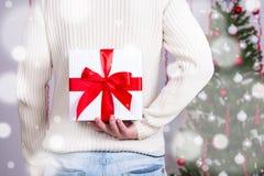 圣诞节概念-供以人员掩藏的礼物盒后边后面 免版税库存照片
