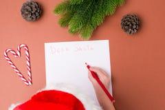 圣诞节概念 信函圣诞老人 在纸,圣诞装饰材料的男孩手在米黄桌上 顶视图 库存图片