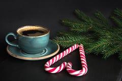圣诞节概念 咖啡和棒棒糖在心脏形状在黑背景与圣诞树分支 库存图片