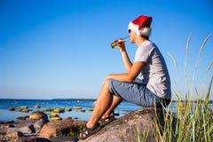 圣诞节概念-圣诞老人帽子饮用的啤酒的英俊的人在t 库存图片