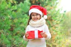 圣诞节概念-圣诞老人红色帽子的愉快的微笑的孩子有箱子礼物的 免版税库存图片