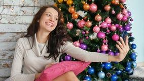 圣诞节概念-拍近selfie照片的少妇装饰了圣诞树 股票视频