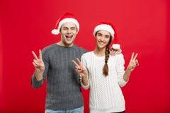 圣诞节概念-显示与手指的画象可爱的年轻夫妇两个手指姿态对照相机 免版税库存照片