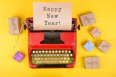 圣诞节概念-有文本& x22的打字机; 新年快乐! & x22; 礼物盒和包装纸在黄色背景 免版税库存照片
