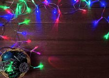 圣诞节欢乐在一个小柳条筐的结构的干燥棕色冷杉木锥体和礼物 免版税库存图片