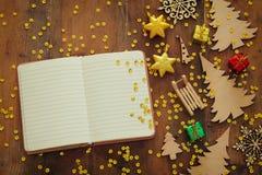 圣诞节欢乐装饰的顶视图图象在空的开放笔记本旁边的在老木背景 库存图片