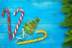圣诞节款待:以云杉、棒棒糖和绿色云杉的分支的形式五颜六色的棒棒糖在一个蓝色木板 库存照片