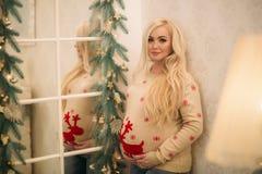 圣诞节毛线衣的一个相当怀孕的金发碧眼的女人在镜子附近站立 免版税库存照片