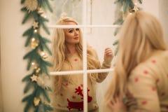 圣诞节毛线衣的一个相当怀孕的金发碧眼的女人在镜子附近站立 免版税库存图片
