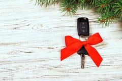 圣诞节汽车钥匙的礼物 汽车钥匙特写镜头视图与红色弓的作为在木土气葡萄酒背景的礼物 免版税图库摄影