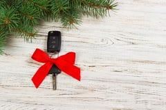 圣诞节汽车钥匙的礼物 汽车钥匙特写镜头视图与红色弓的作为在木背景的礼物 免版税库存图片