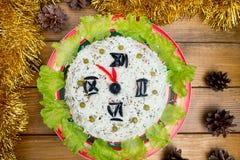 圣诞节沙拉米橄榄绿豌豆-概念新年时钟表盘,午夜,棕色木背景云杉 免版税库存照片