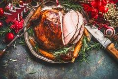 圣诞节火腿服务与烤菜和欢乐装饰在葡萄酒背景在减速火箭的颜色,顶视图,地方tex的 免版税库存图片