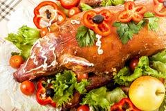 圣诞节烘烤在宴会桌上的乳猪 免版税库存图片