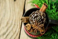 圣诞节烘烤成份肉桂条茴香星丁香在葡萄酒水罐的杉木锥体有在木头的红色丝带杜松枝杈的 库存图片