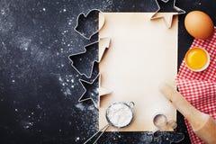 圣诞节烘烤的食物背景 曲奇饼切削刀、面粉、滚针、鸡蛋和纸板料在厨房用桌顶视图 库存照片