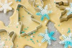 圣诞节烘烤背景:面团、曲奇饼切削刀和雪花 图库摄影