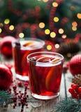 圣诞节热的蔓越桔茶、橙色石榴拳打或者被仔细考虑的酒在一张土气木桌里 特写镜头 库存照片
