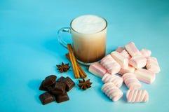 圣诞节热的饮料可可粉咖啡或巧克力与牛奶奶油和蛋白软糖在一小透明杯在蓝色背景 库存图片