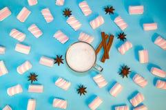 圣诞节热的饮料可可粉咖啡或巧克力与牛奶奶油和蛋白软糖在一小透明杯在蓝色背景 免版税库存图片