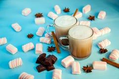 圣诞节热的饮料可可粉咖啡或巧克力与牛奶奶油和蛋白软糖在一小透明杯在蓝色背景 免版税图库摄影